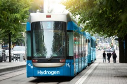 A hydrogen fuel cell tram stands at the station