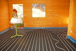 A hydronic closed loop underfloor heating system laid out on a molded insulated panel in EPS with a spooling table inside a partially constructed wooden house