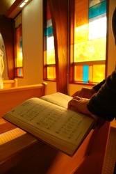 A hymn book inside a church being red by a woman.