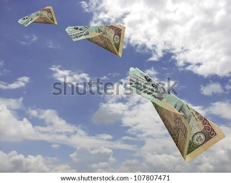 A image showing an aeroplane made up of Indian 100 Rs. note flying in air.All planes clipping path are in the file.This can be conceptual image for online Indian money transfer or like that.
