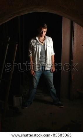 A intense man standing in the dark
