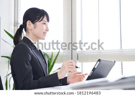 A Japanese female businesswoman uses a tablet in the office for interviews
