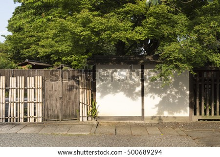 A Japanese Garden With A Big Green Maple Tree, Bamboo Fence And White Wall
