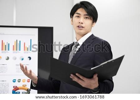 A Japanese male businessman giving a presentation.