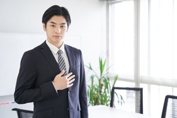 A Japanese male businessman puts his hand on his chest in a conference room
