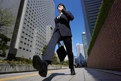A Japanese male businessman walks briskly through an office district.
