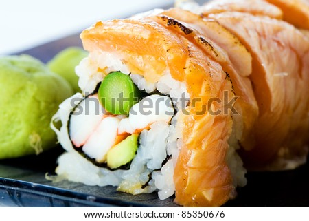 A Japanese seafood Sushi roll with fresh salmon seared rare, asparagus, wasabi and more.