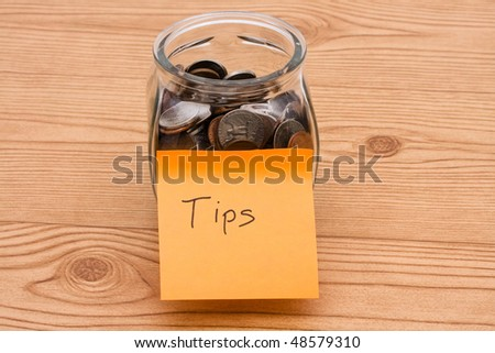 A jar full of change sitting on a wooden background, Tips are appreciated
