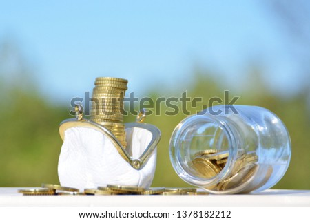 A jar full of savings stands on a space next to a purse of saved coins that pile up to form a tall tower - saving concept with room for text or other items #1378182212
