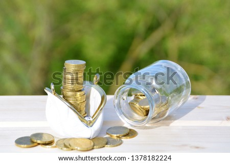 A jar full of savings stands on a space next to a purse of saved coins that pile up to form a tall tower - saving concept with room for text or other items #1378182224