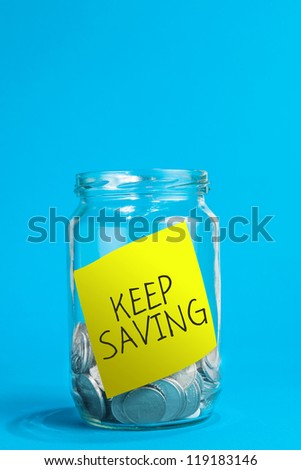 A jar of coins, with keep saving reminder note inside the jar.