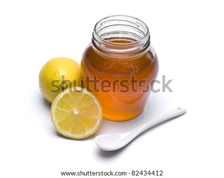 A jar of honey, lemons and spoon. Isolated on white background.