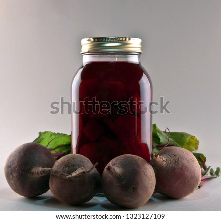A jar of pickled beets and some freshly picked beets