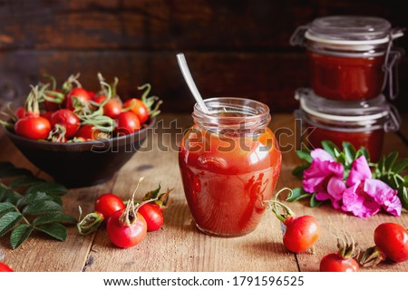 A jar of rose hip jelly and fresh rose hips on wooden table.  Stock photo ©