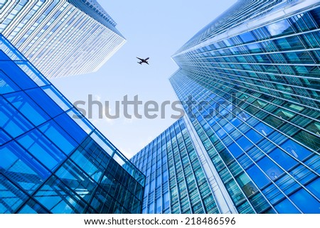 A jet airplane silhouette with business office building towers in London #218486596