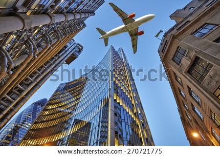 Shutterstock A jet plane flying low over Three different kind of architecture with commercial office buildings exterior. Evening view at bottom skyscrapers.