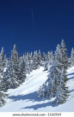 A jet plane rises almost vertically into the sky, leaving a contrail, above snow-covered trees on a mountainside.