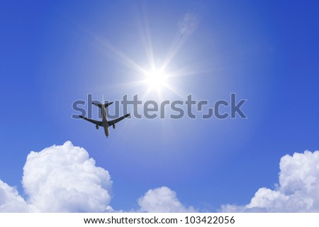 A jetliner aeroplane flying over white clouds and sun