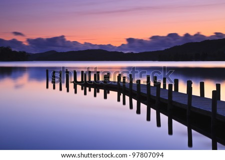 A jetty reflected in the still water of Coniston Water at sunset - stock photo