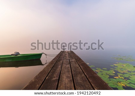 A jetty with boat shrouded in fog in warm morning light in Bavaria. Soothing landscape photo of Hopfensee lake in Allgäu. Well suited for quotes or as background. Photo stock ©