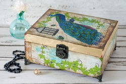 A jewellery box decoupaged with a Peacock and gilded with gold leaf