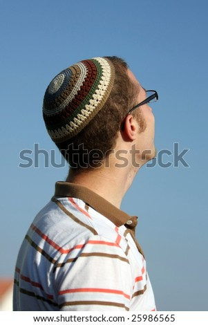 A Jewish Young Adult with a knitted skull cap looks up