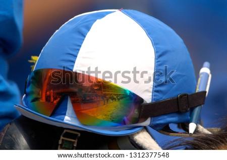 de17351e03e10 A jockey's helmet and sun glasses on a race day #1312377548