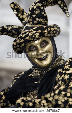A joker at the Venice carnival in St. Mark's Square in a gold and black costume