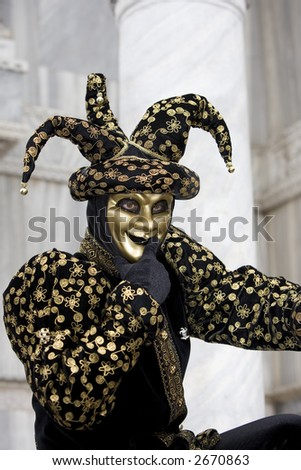 A joker thinking at the Venice carnival in St. Mark's Square in a gold and black costume