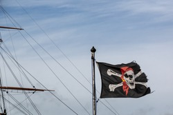 A jolly roger or skull and crossbones flag flying in front of the mast of an old ship