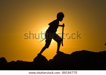 A joy boy is playing on the rocks of a pier with wooden sticks during dawn.