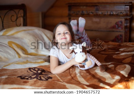 A joyful, beautiful girl is holding a toy cow and lying on a sunny morning on a bed in the bedroom of a rustic log house. Stock photo ©