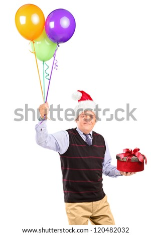 A joyful mature gentleman with christmas hat holding gift and bunch of balloons in his hands isolated on white background