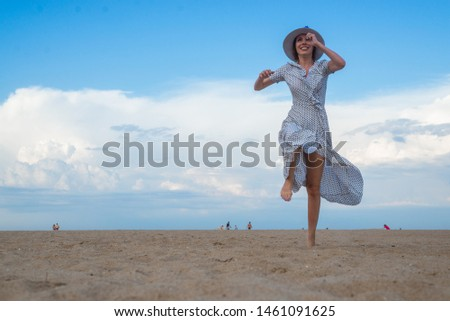 A joyful middle-aged woman in a dress runs and jumps along the seashore of the ocean. Joy, pleasure, rest, freedom concept.
