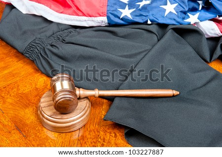 A judge�s gown and gavel with sound block on deep, rich colored wooden desktop and American flag