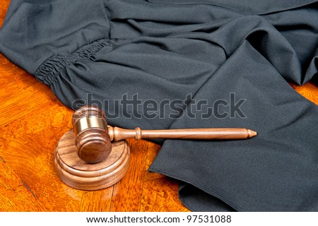 A judges gown and gavel with sound block on deep, rich colored wooden desktop