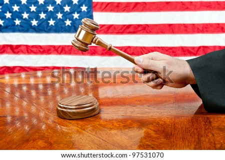 A judges gown and gavel with sound block on deep, rich colored wooden desktop and American flag