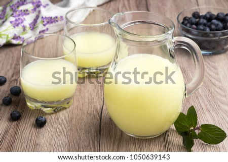 A jug of fresh whey with two glasses of whey and fresh blueberries