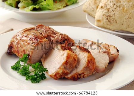 A juicy fresh pork loin roast sliced on a plate