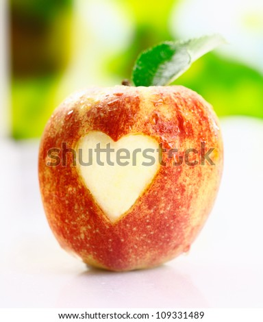 A juicy fresh ripe red apple with an incised heart shape in the skin conceptual of I love apples