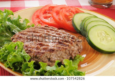 A juicy grilled ground beef patty with cucumbers nad lettuce