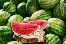 A juicy ripe watermelon, cut up, lies on a pile of other watermelons. Red watermelon looks delicious lying in the sun on other watermelons.