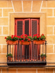 A juliet balcony with red louvre doors and small red flowers in window planters