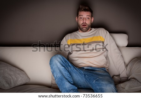 A jumpy man watching a scary movie