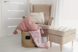 A jute handmade basket with a small black chalkboard and pillows and a pink blanket on the floor next to a beige armchair  with a pouf on a white wallpaper background. Cozy home concept