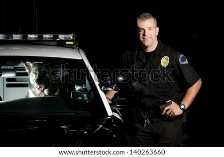 A K9 handler standing next to his patrol car with his partner in the driver seat.