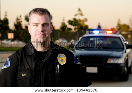 A K9 police officer standing in front of his patrol car at dusk.