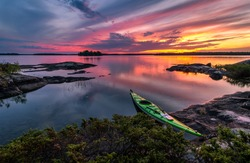 A kayak stopped on the shore of Eagle Lake at sunset on a calm evening in Northwest Ontario, Canada