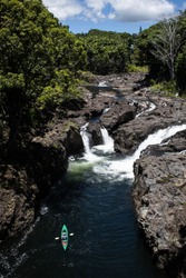 A kayaker in a green kayak on a river paddling upstream toward a waterfall