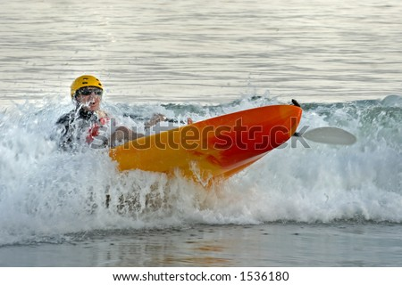 A kayaker paddles through the surf and nearly capsizes his kayak.